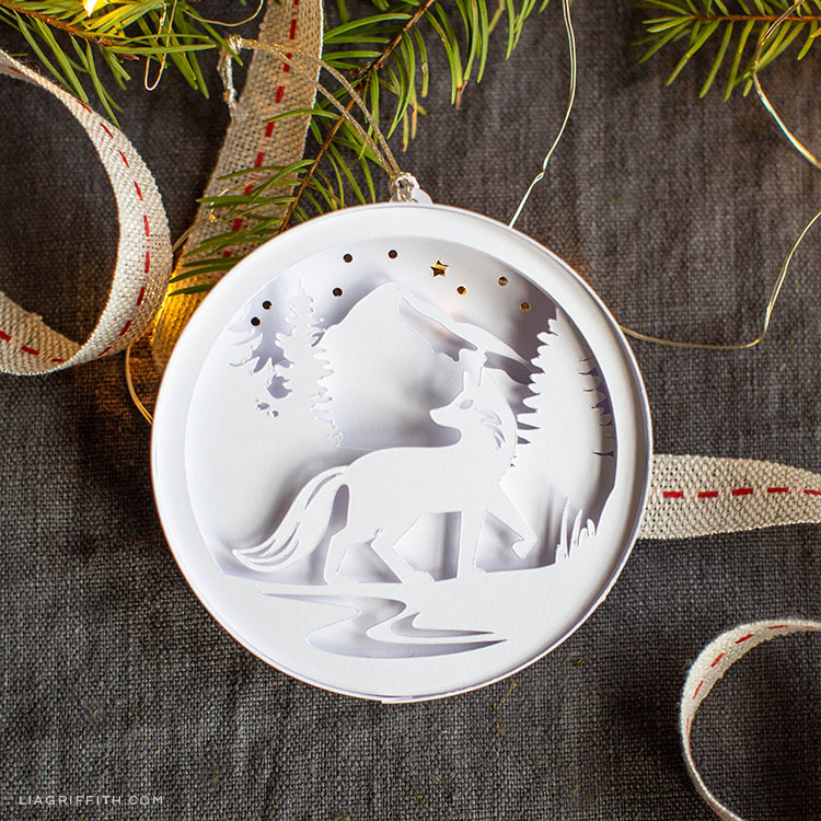 3D paper woodland ornament featuring a wolf in front of trees in the snow