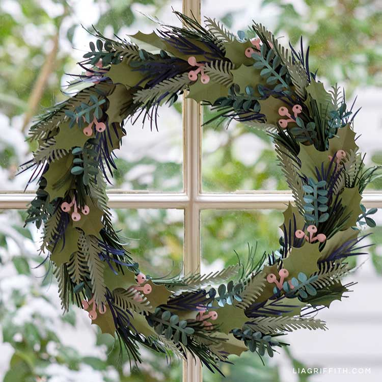 winter greens and pink berry wreath hanging on window