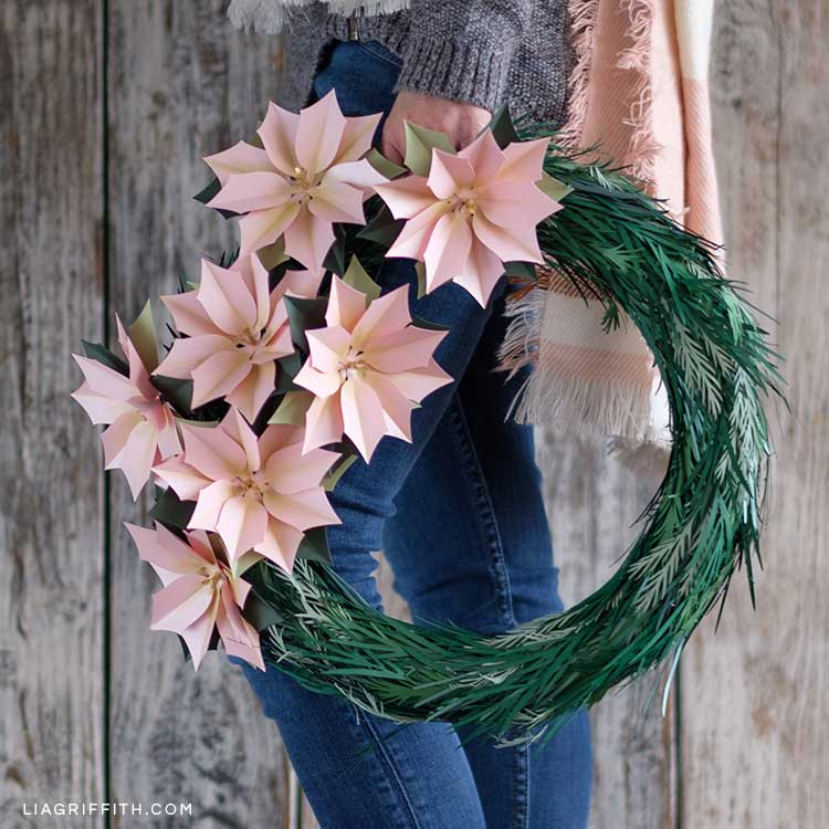 Woman holding pink frosted paper poinsettia wreath