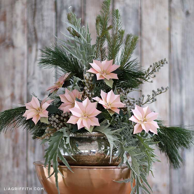 floral arrangement with pink frosted paper poinsettias and fresh greenery