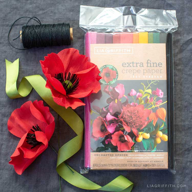 extra fine crepe paper poppy flowers next to black thread and Lia Griffith's Enchanted Garden collection of extra fine crepe paper