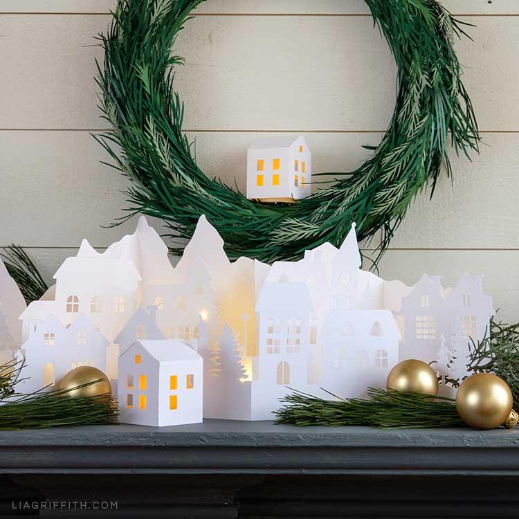 Paper village scene on mantel below DIY paper wreath