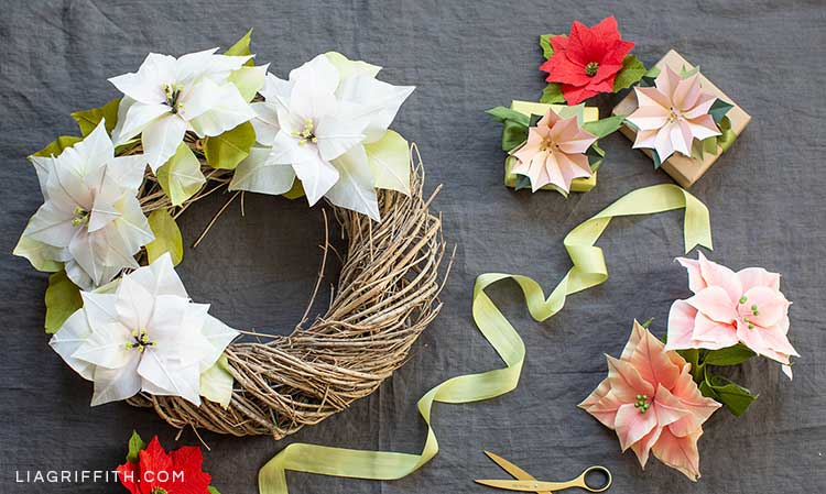 paper poinsettia wreath and paper poinsettia gift toppers next to ribbon and scissors