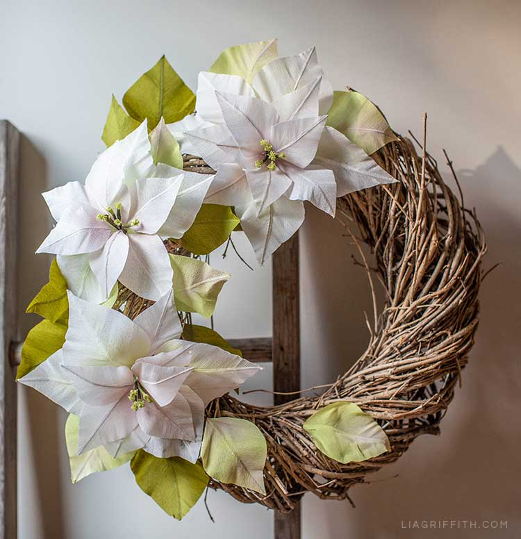 white crepe paper poinsettia wreath hanging on wood ladder