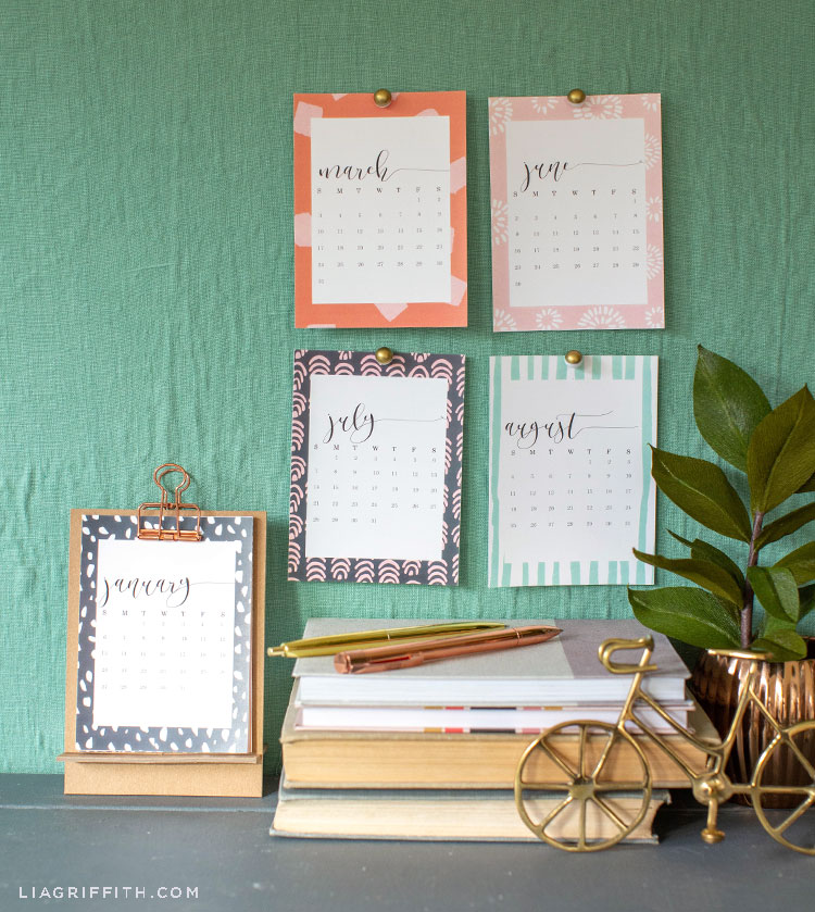 2019 desktop calendar with chipboard stand and monthly calendar pages hanging on wall above books, pens, small gold bike décor, and potted plant