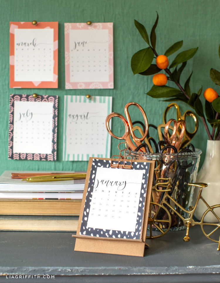 2019 desktop calendar in front of scissors, small gold bike, paper kumquats in vase, books, pens, and monthly calendar pages on wall