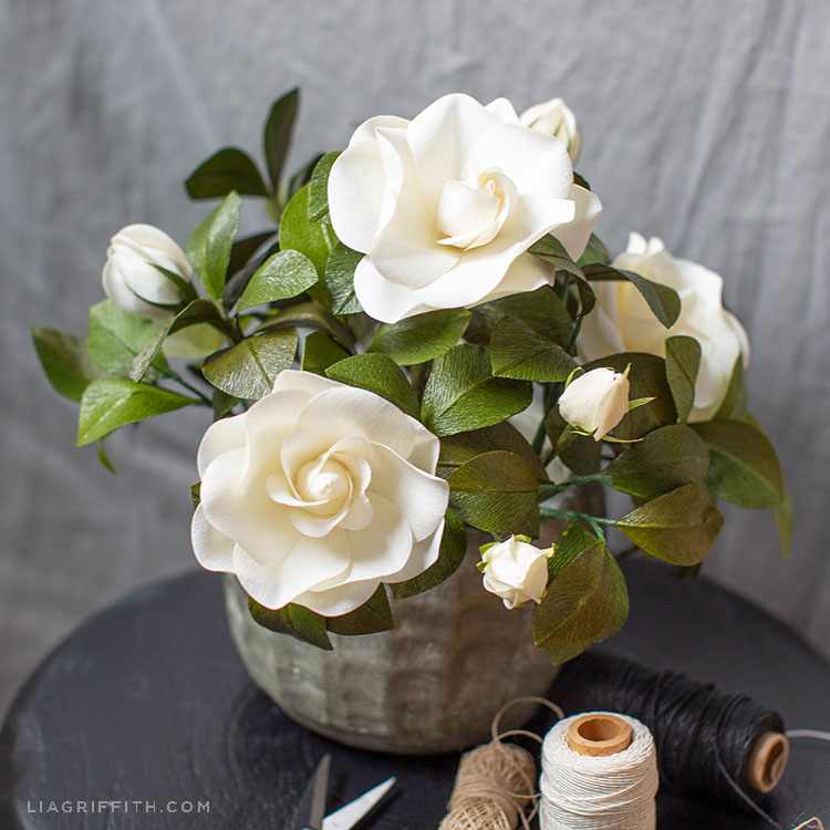 white crepe paper gardenia plant in grey pot next to spools of thread
