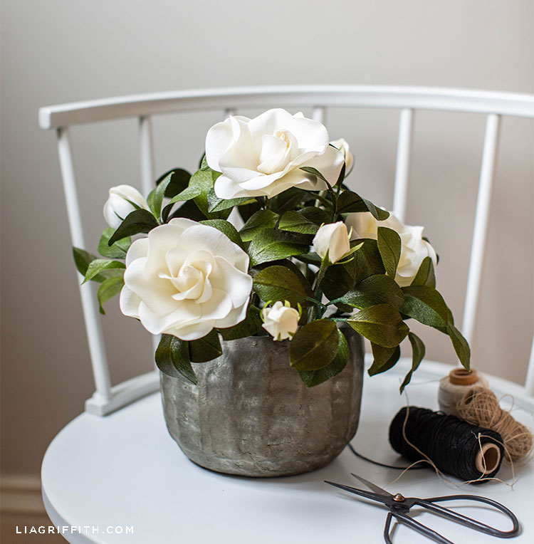 white crepe paper gardenia plant on white chair next to scissors and spools of thread
