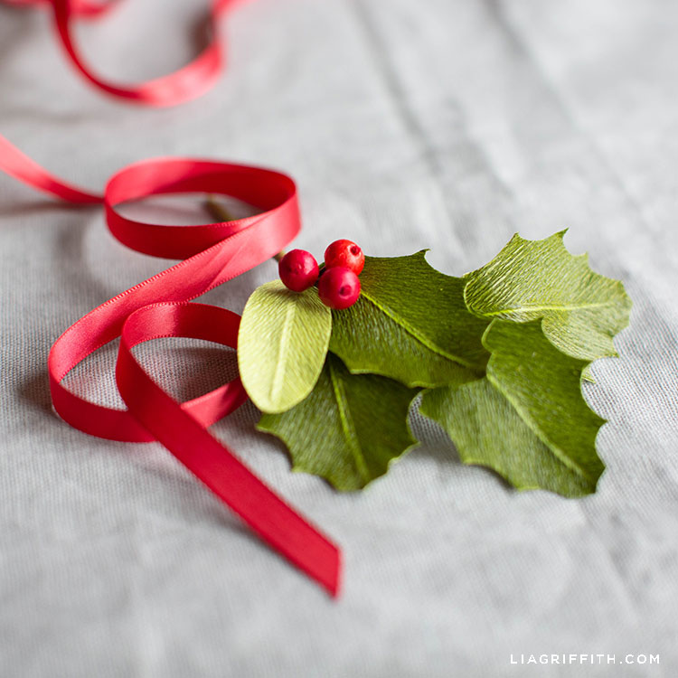 paper holly leaves with red berries and red ribbon