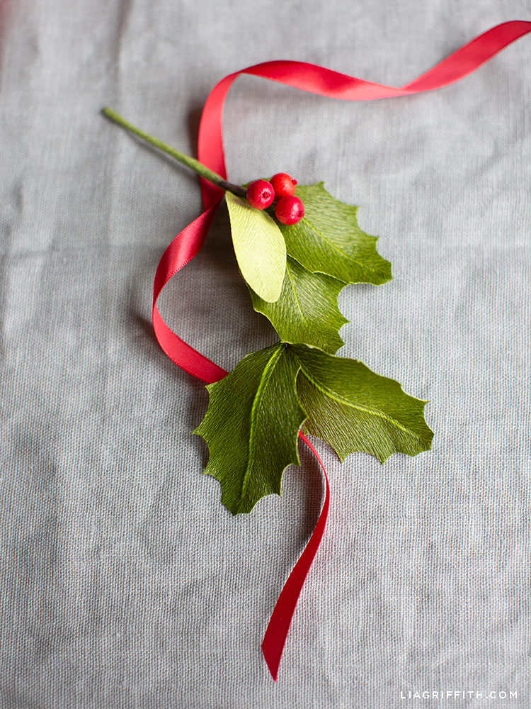 paper holly leaves and red berries with red ribbon
