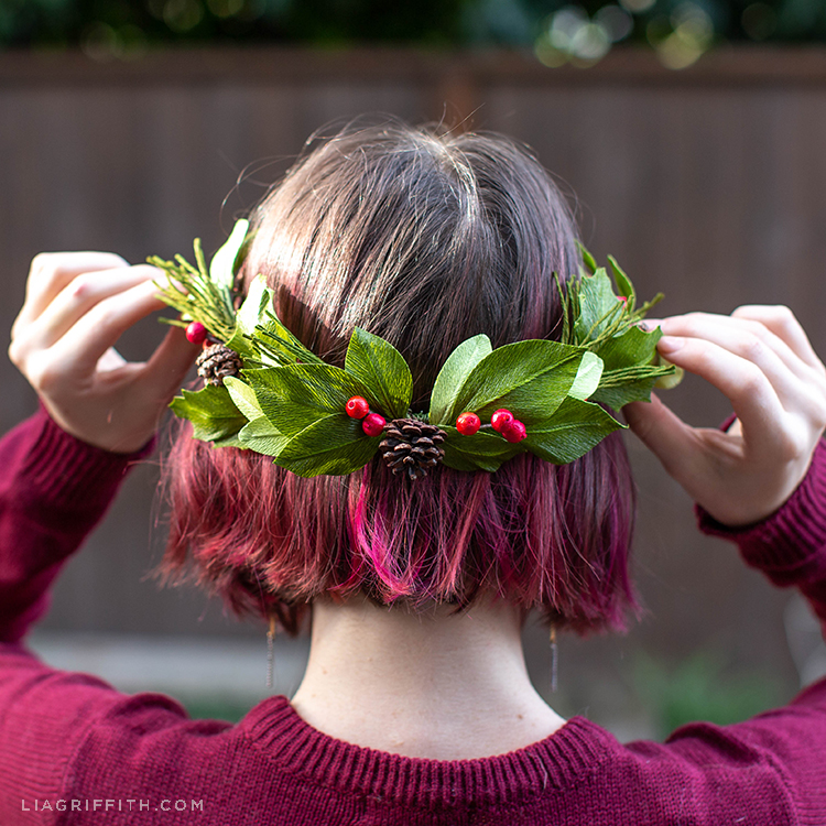 Woman putting crepe paper winter evergreen wreath on her head
