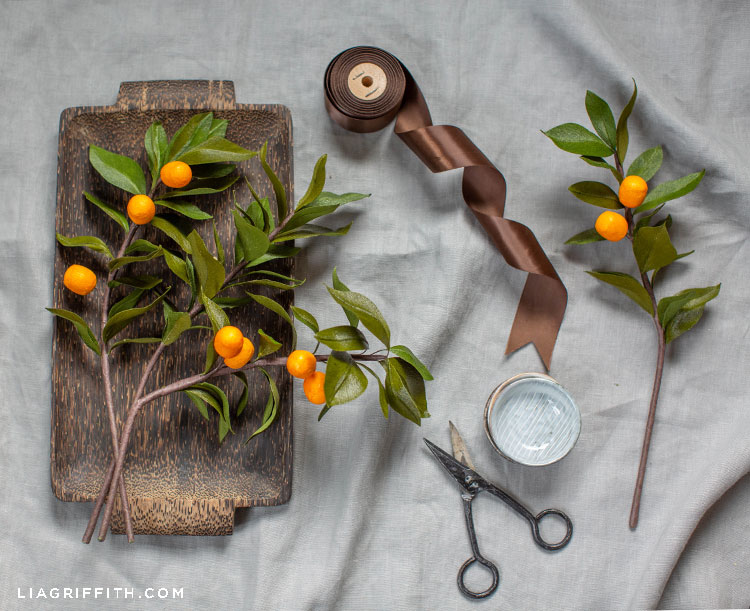 crepe paper kumquat branches on wood tray next to scissors and brown ribbon