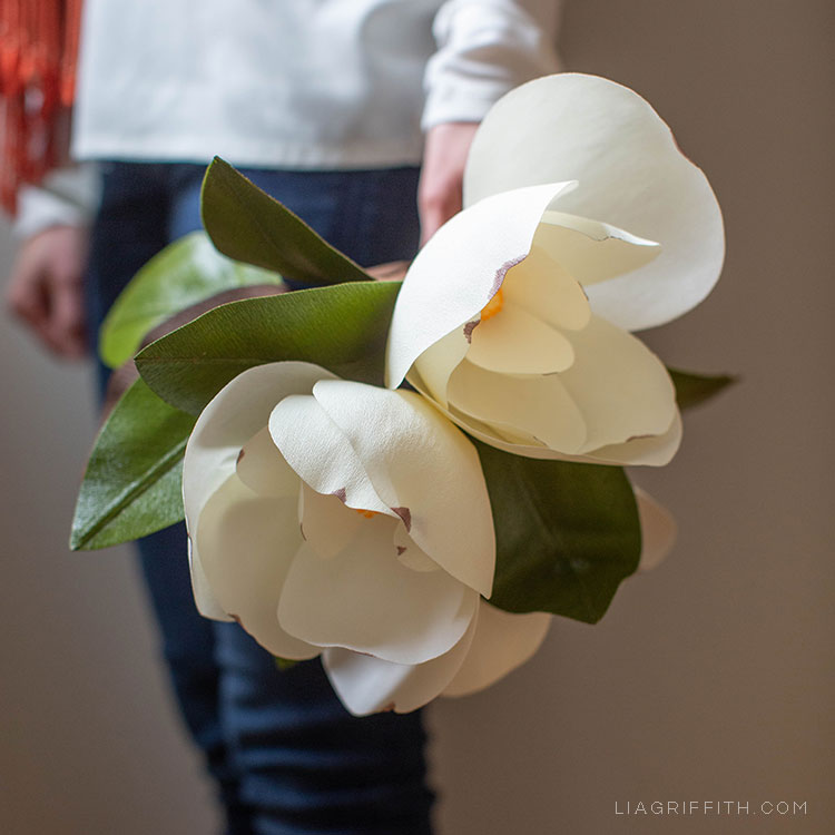 Person holding crepe paper magnolias