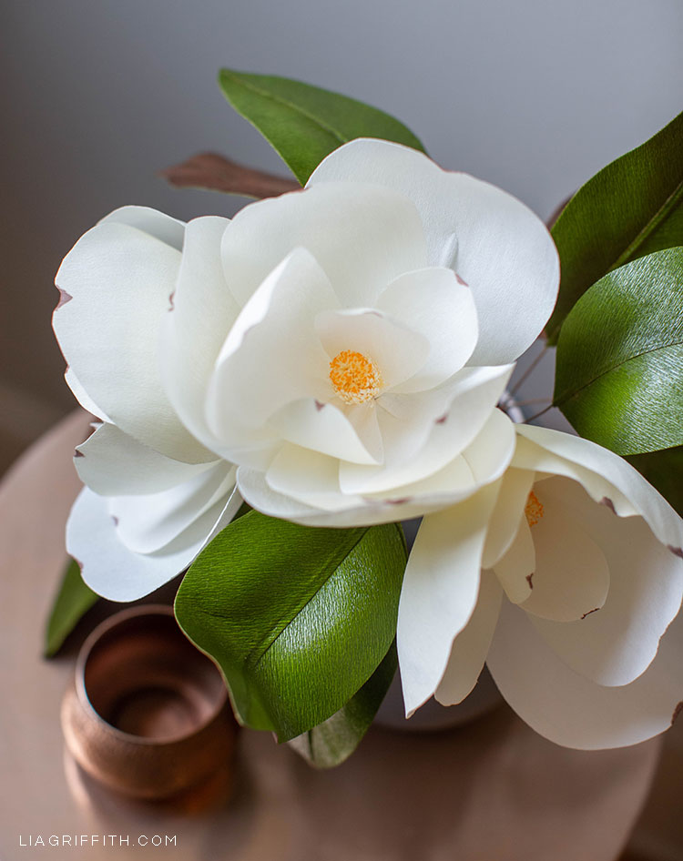 white crepe paper magnolia flowers with green leaves
