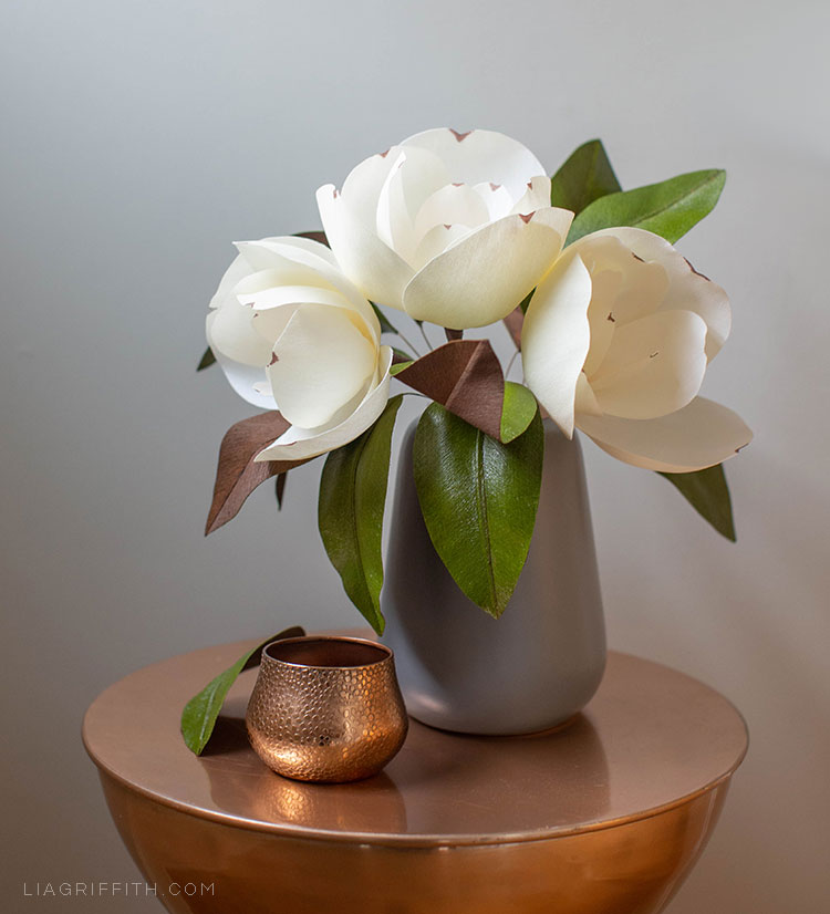 creamy white crepe paper magnolias in grey vase on copper table