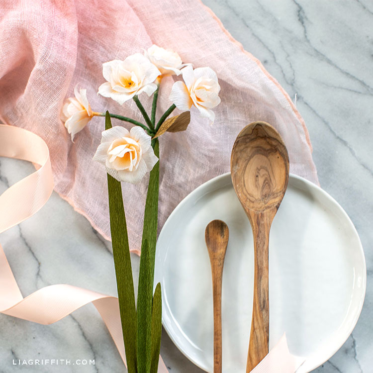 crepe paper double daffodils next to white plate and wooden spoons with pink ribbon and pink scarf