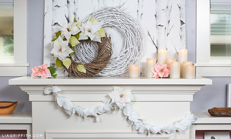 holiday mantel with white crepe paper poinsettia wreath, pink crepe paper poinsettias, white twig branch wreath, white crepe paper magnolia leaf garland, and candles