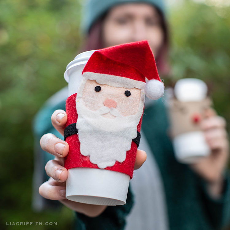 Woman holding out coffee cup with felt Santa cozy