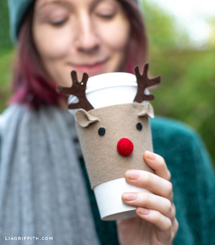 Woman holding coffee cup with felt reindeer cozy