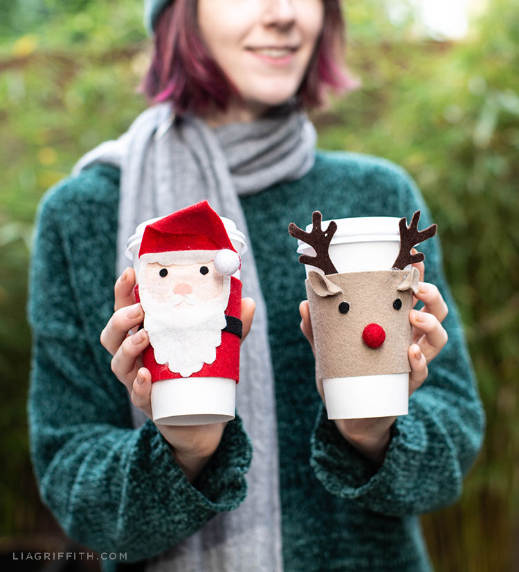 Woman holding coffee cups with felt Christmas coffee cup cozies