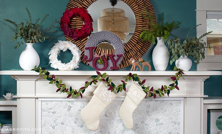 holiday mantel with felt greenery garland, felt monogrammed white stockings, felt joy, felt reindeer, red ombré felt wreath, white felt wreath, grey knit wreath, and white vases with fresh greenery