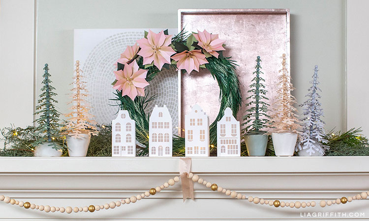 holiday mantel with green garland and tiny LED string lights, paper poinsettia wreath, paper canal houses, paper snowflake trees, wooden bead garland, pink tray, and artwork