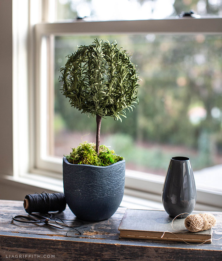 paper rosemary topiary in front of window next to mini grey vase, black and beige thread, scissors, and book