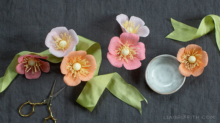crepe wild roses with green ribbon, scissors, and small bowl