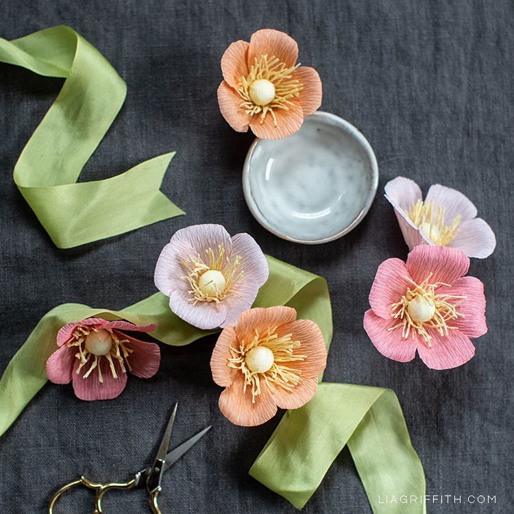 crepe wild roses with green ribbon, small white bowl, and scissors