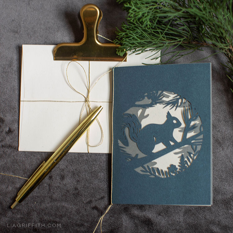 papercut woodland holiday card featuring squirrel next to envelopes with gold clip and gold pen