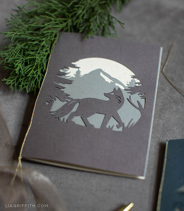 papercut woodland holiday card with fox in the forest and mountain in the background