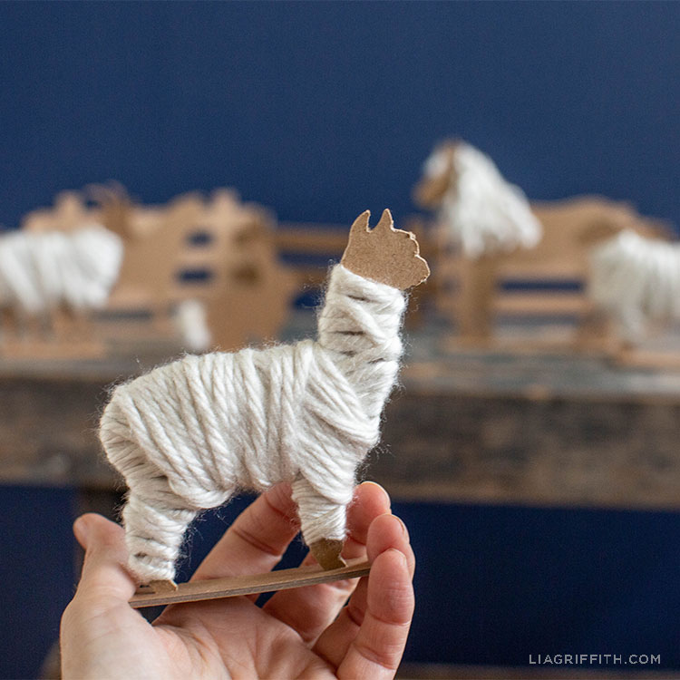 person holding chipboard llama wrapped in yarn