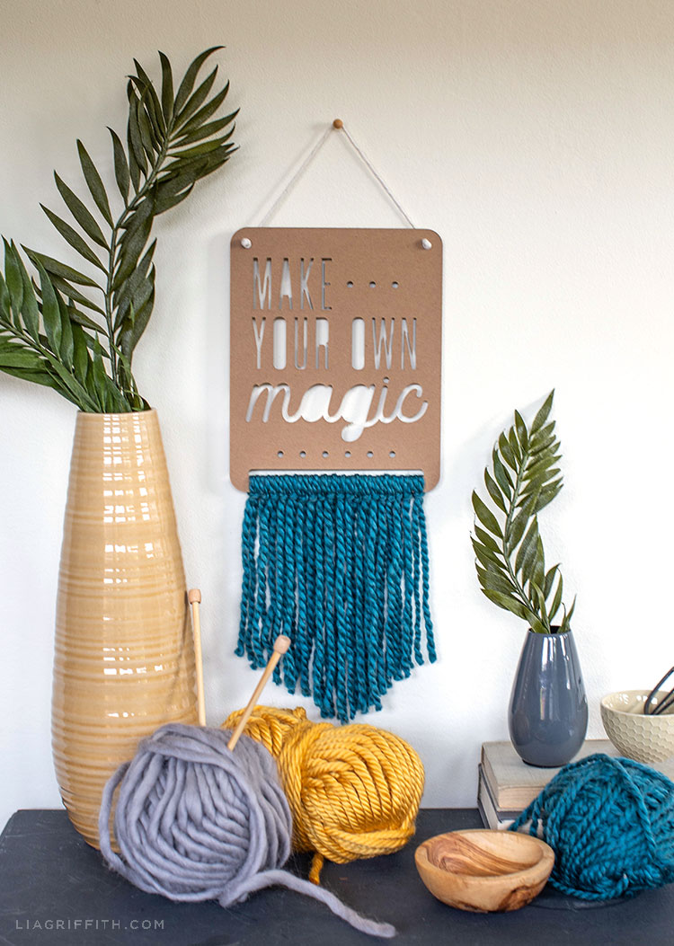 make your own magic chipboard and yarn wall hanging next to vases with greenery and yarn