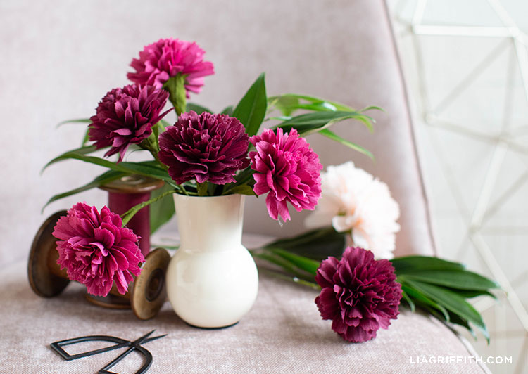 crepe paper carnations inside and outside of white vase