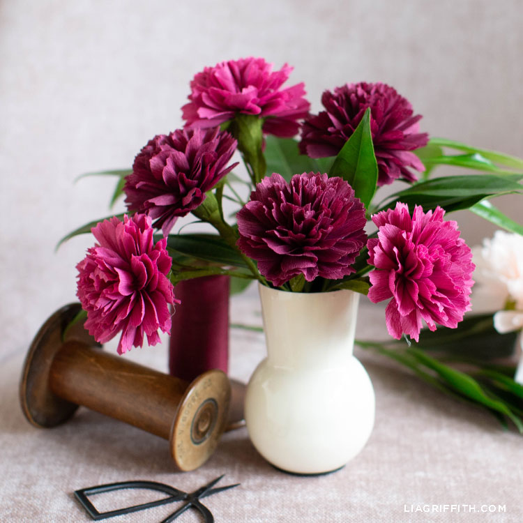 crepe paper carnations in white vase next to thread spool and scissors