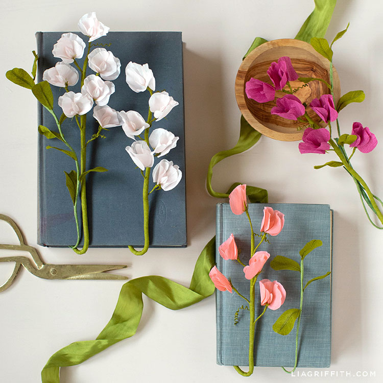 crepe paper sweet peas on books and wooden bowl with green ribbon
