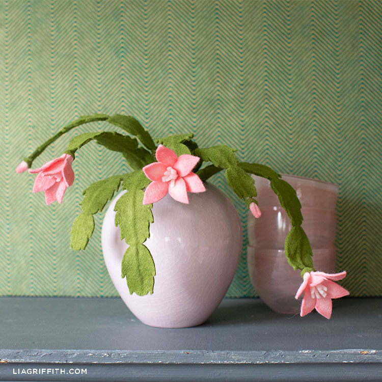 pink felt holiday cactus in pink pot next to pink bowls on grey mantel with green wall