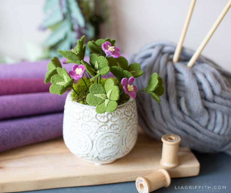 felt clover plant in white vase next to purple felt, grey yarn, and spools