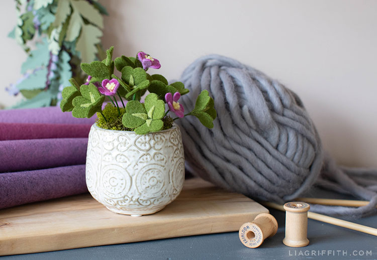 felt clover plant in white vase on wood board next to purple felt, grey yarn, and spools