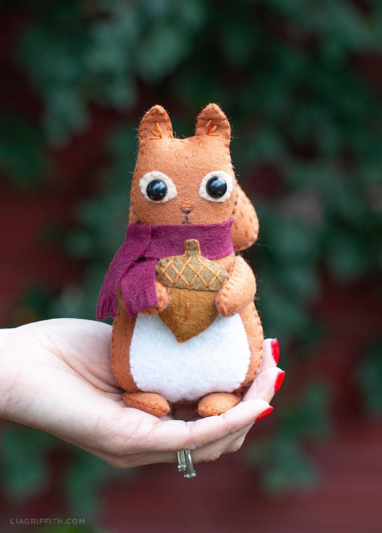 Woman's hand holding felt squirrel stuffie