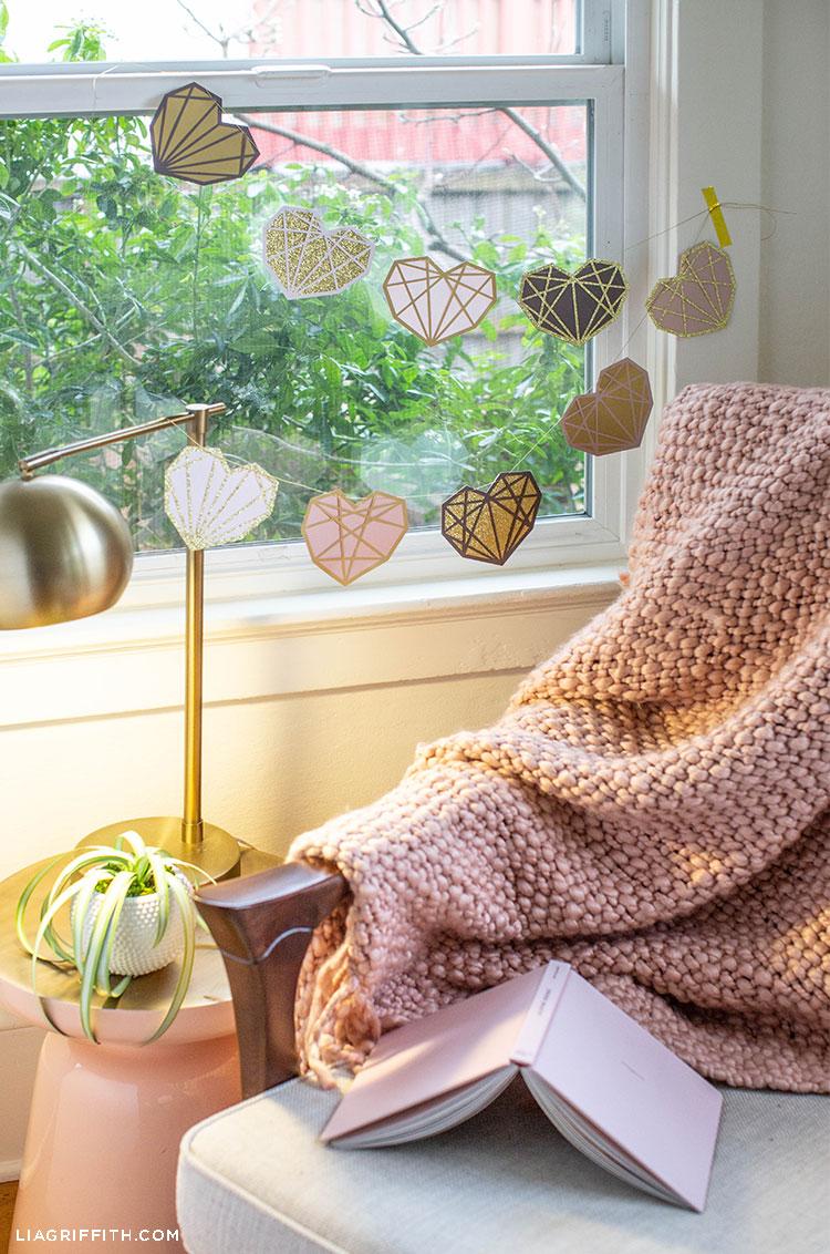 papercut geometric heart garland hanging across window in corner of living room