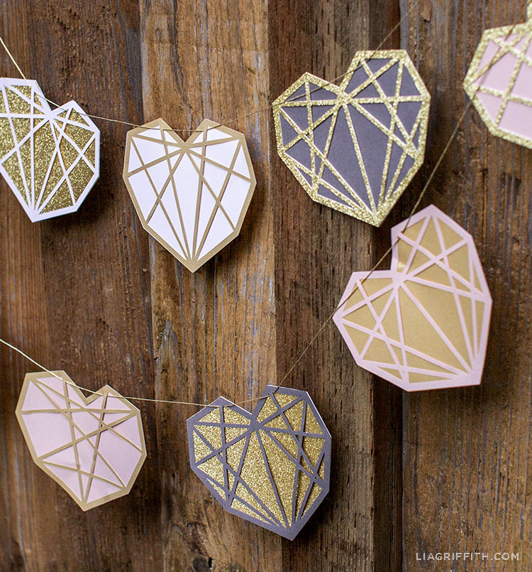 papercut geometric heart garland hanging on fence