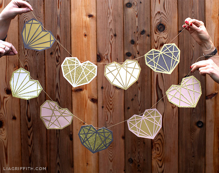 Two pairs of hands holding papercut geometric heart garland in front of fence