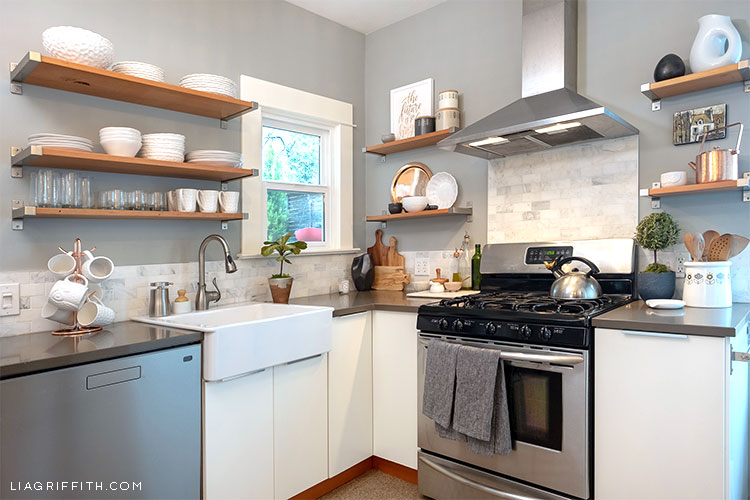 kitchen with open shelves, stove, and sink