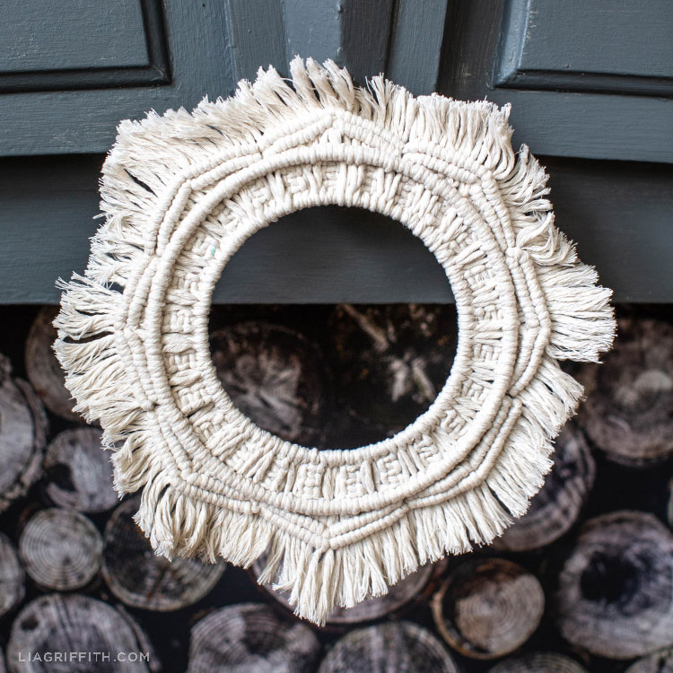 macramé wreath hanging on mantel above fireplace