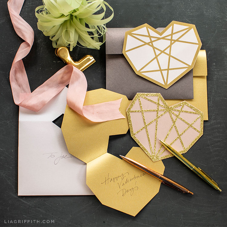 paper geometric heart cards with handwritten note for Valentine's Day, pink ribbon, and paper air plant