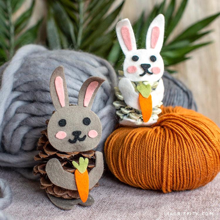 felt pinecone bunnies sitting by yarn