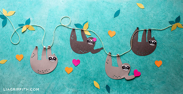papercut sloth gift tags hanging on twine with paper hearts, flowers, and leaves in background