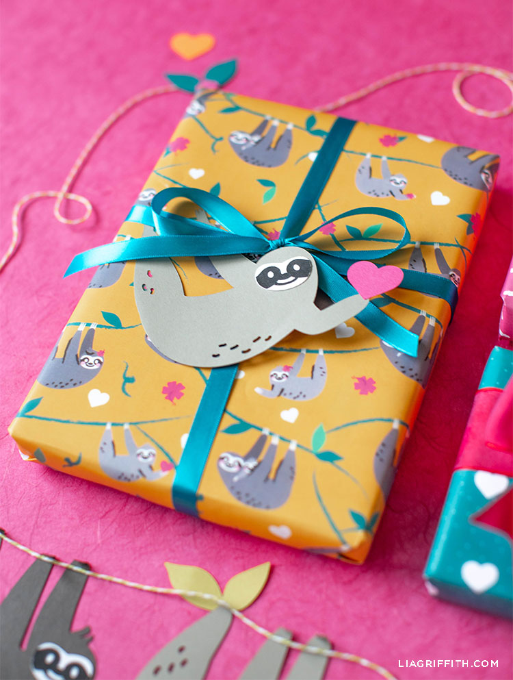 printable sloth wrapping paper with bow and sloth gift tag against pink background