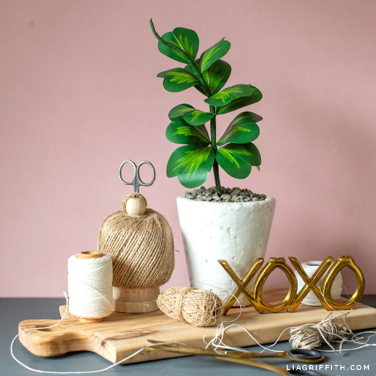 paper Hoya Kerrii plant in white pot on wooden board next to XOXO sign, twine, and scissors